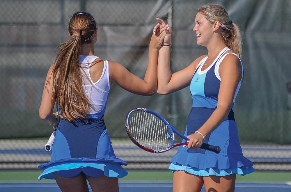 GVL / Hannah Mico. Doubles partners Leah Dancz and Kali Phillips (both juniors) congratulate each other on a well-played set at Saturday's match against Wayne State Univeristy, before heading off to their next  set.