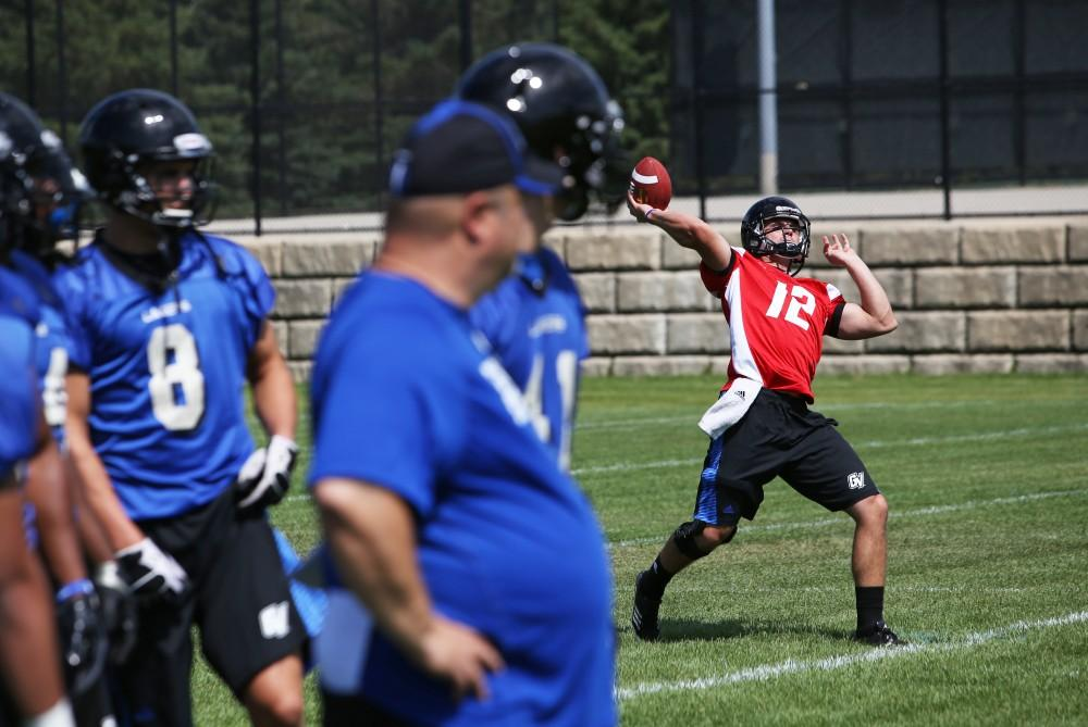 GVL/Kevin Sielaff #12, Heath Parling, preparing himself and his receivers for the highly-anticipated fall season opener of the Grand Valley State University football team. The team practiced just outside Lubbers Stadium this past Thursday, August 14th.