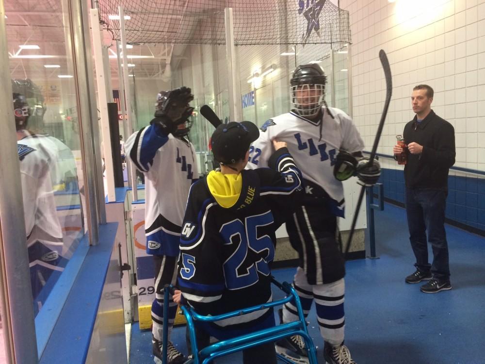<p>Nathan Vandyken congratulates GVSU hockey players after their win over Davenport.</p>
