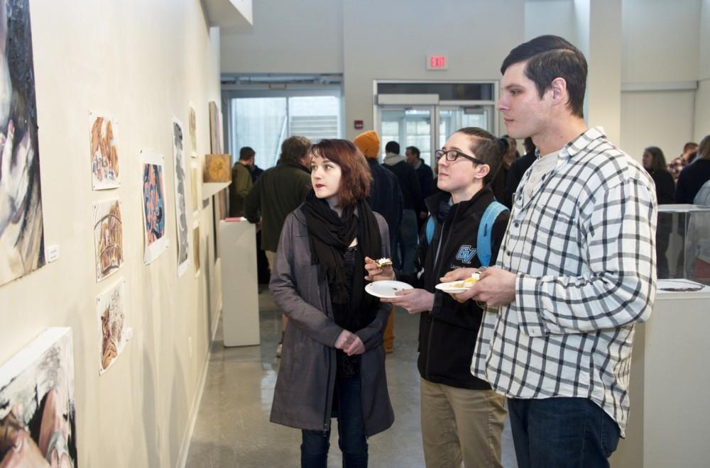 GVL / Courtesy - GVSU University CommunicationsLauren Kohler (middle) and Sam Adamczyk (right) observe the 5th Annual Juried Art Show inside of the Calder Art Center.