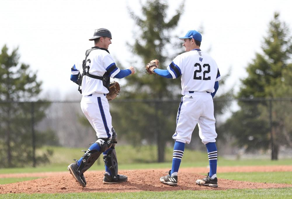 GVL/Kevin Sielaff - Tate Brawley (22) and Connor Glick (16) fist bump at the mound after closing out an inning during the game vs. Ashland on Wednesday, April 12, 2017.