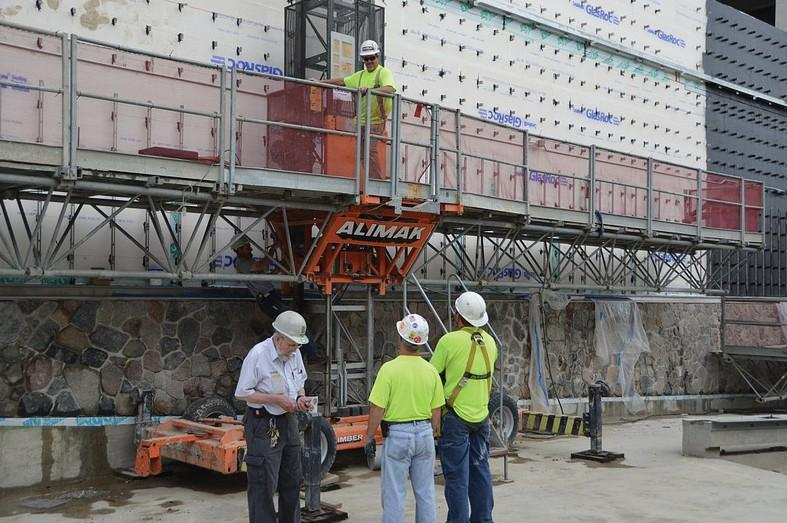 Courtesy Photo / GVSU LibraryConstruction workers discuss the east exterior of the new Mary Idema Pew library.