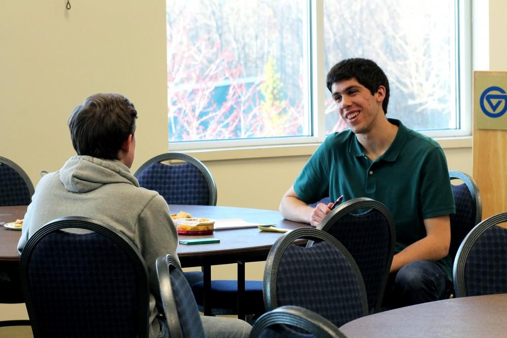 GVL/Sara CarteBrad Mueller, a student at Grand Valley, explains to another student about the Interfaith Service and Dialogue event for the Better Together Days events on April 14, 2015 in the Kirkhof Center, Allendale.