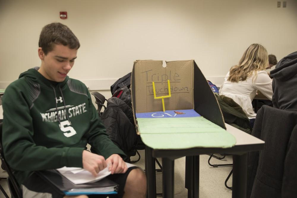 GVL / Luke Holmes - Brian Trager makes final preparations for his Grand Valley football themed game. Students worked on their projects in Mackinac Hall for the Cardboard Challenge Friday, Feb. 19, 2016.
