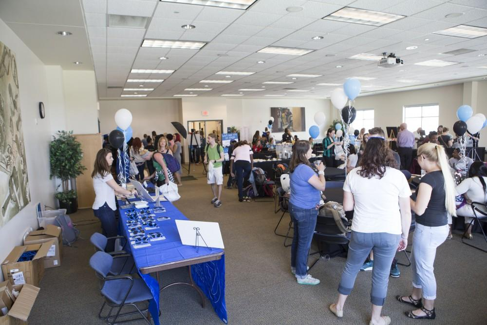 GVL / Sara Carte - Seniors attend GradFest to get their pictures taken, pick up cap and gowns, and win free prizes in the Kirkhof Center on Monday, Apr. 18, 2016.