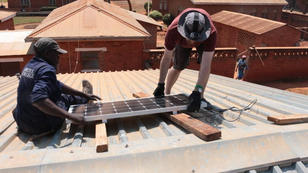 GVL / Courtesy - Patrick McCarthy GVSU student Patrick McCarthy installs a solar panel on the room of Embangweni Mission Hospital in northwest Malawi, Africa.