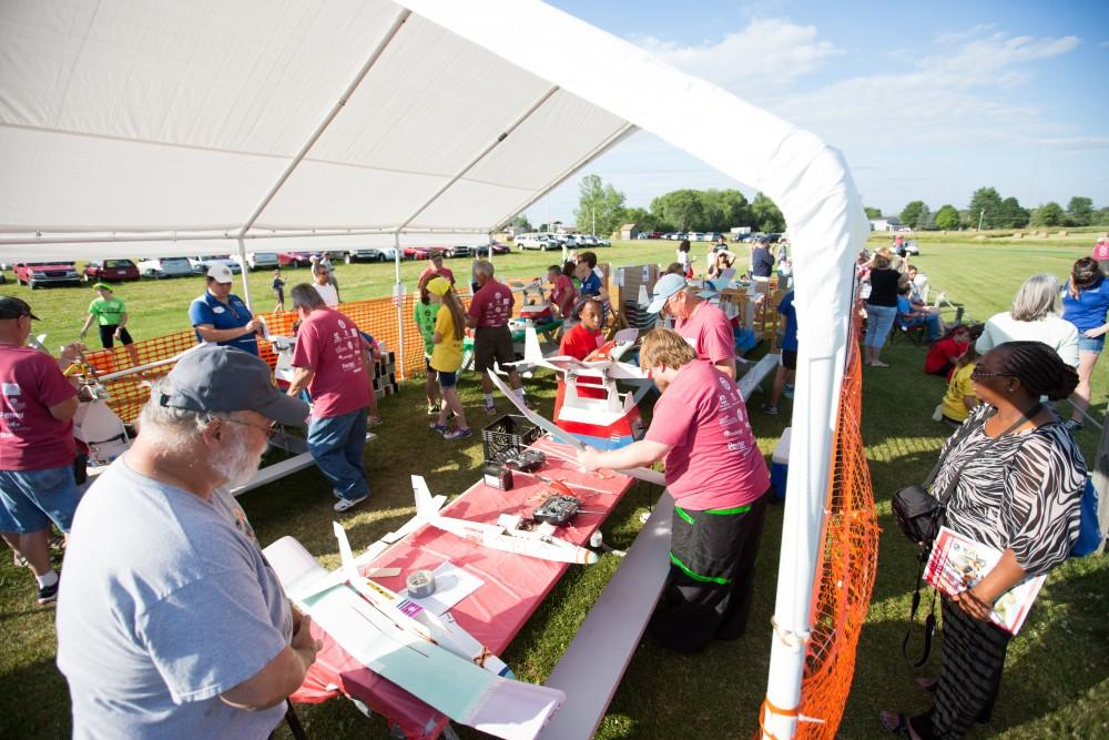 GVL / Kevin Sielaff - Volunteers help repair and assemble plane parts next to the launch site. Students of STEPS (Science, Technology, and Engineering Day Camps) fly planes that they have built during camp at Warped Wings Fly Field in Allendale on Thursday, June 23, 2016.