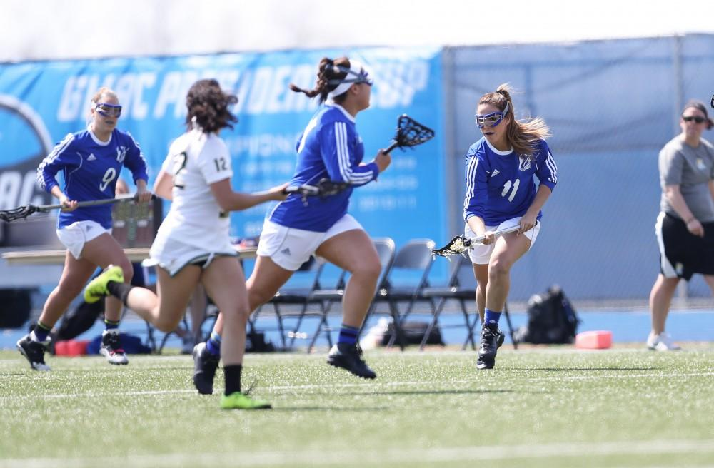 GVL/Kevin Sielaff - Annie Yost (11) gathers the ball and passes it up field during the game vs Northern Michigan on Saturday, April 15, 2017.
