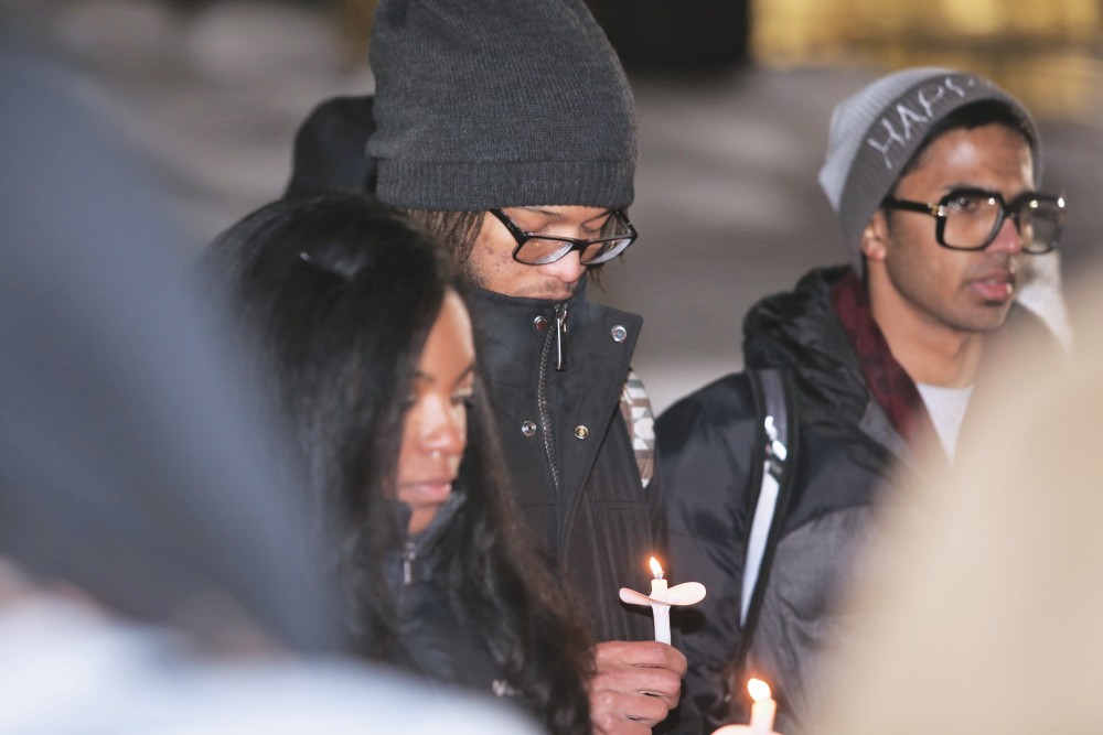 GVL/Kevin Sielaff - Brandon Fitzgerald participates in a candle light vigil around the Cook Carillon Tower on Grand Valleys Allendale campus on Wednesday, Feb. 18, 2015.