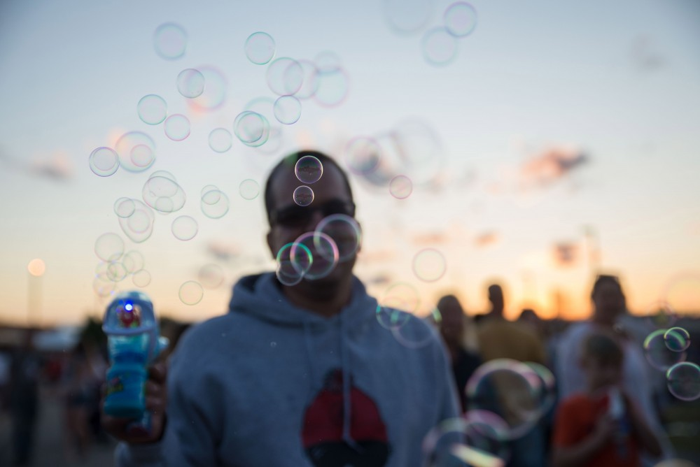 GVL / Luke Holmes - A man fires bubbles from his bubble-gun. The Michigan Challenge Balloonfest was held in Howell, MI on Saturday, June 24, 2017.