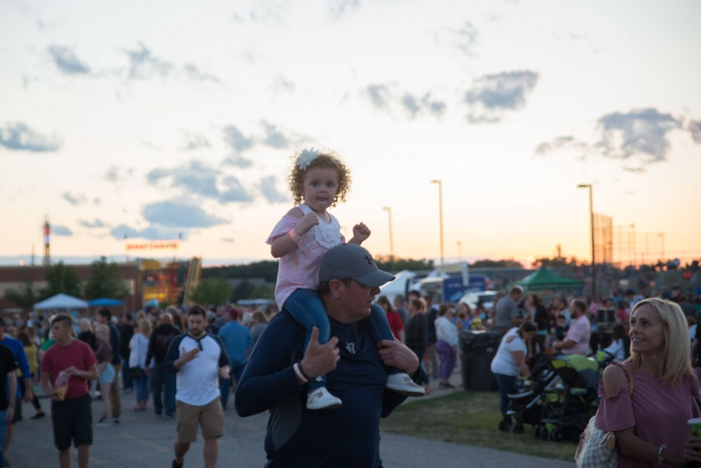 GVL / Luke Holmes - A father carries his daughter on his shoulders. The Michigan Challenge Balloonfest was held in Howell, MI on Saturday, June 24, 2017.