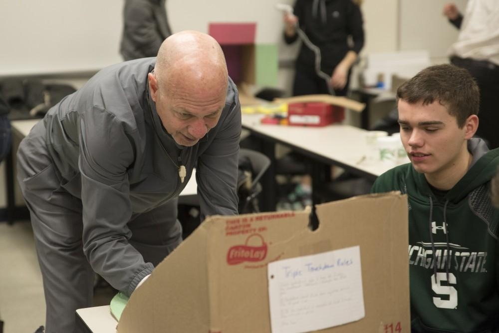 GVL / Luke Holmes - Professor Kilbourne tries out Brian Trager's football game. Students worked on their projects in Mackinac Hall for the Cardboard Challenge Friday, Feb. 19, 2016.