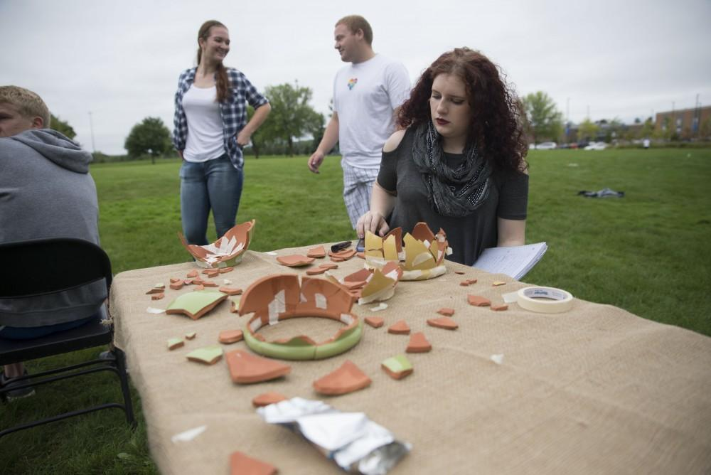 GVL / Luke Holmes - Madison Rogers puts back together a broken pot. The Paleo-Olympics were held in the KC West Lawn on Friday, Sept. 23, 2016.