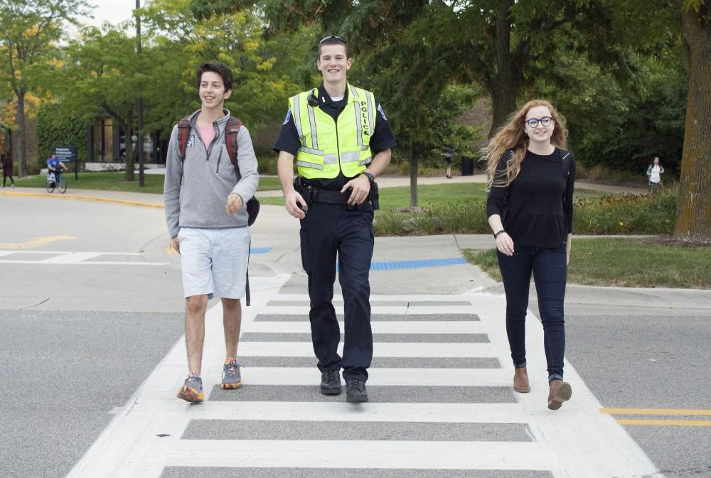 GVL / Emily Frye Officer Andrew Hintz assists GVSU students, Robbie Triano and Becky Oppman, across the street on Wednesday September 13, 2017.