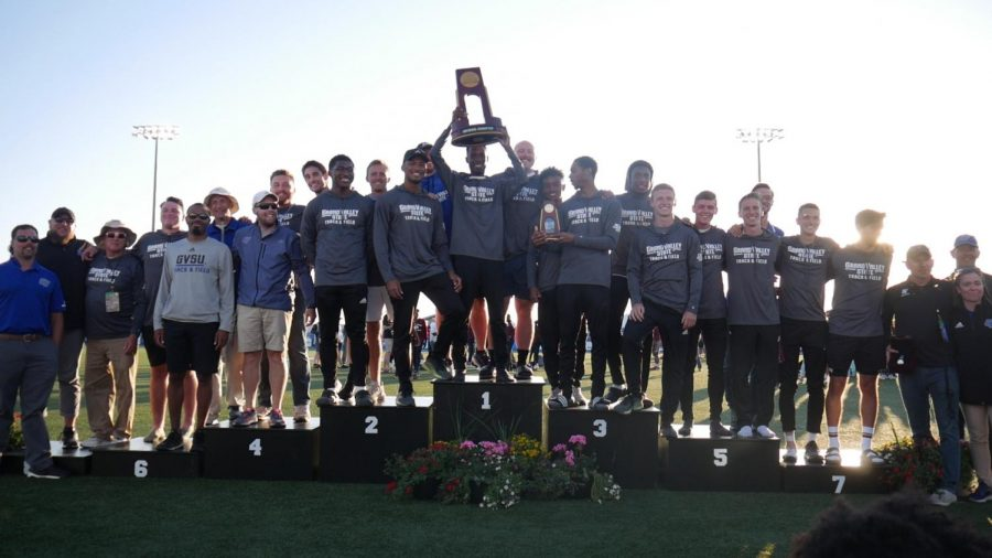 The men's team holds up their trophy at the GVSU Lacrosse/Track and Field Stadium as DII National Champions for the first time.